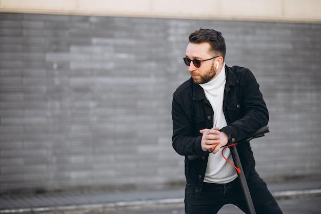 Knappe man rijden in de stad op scooter Gratis Foto