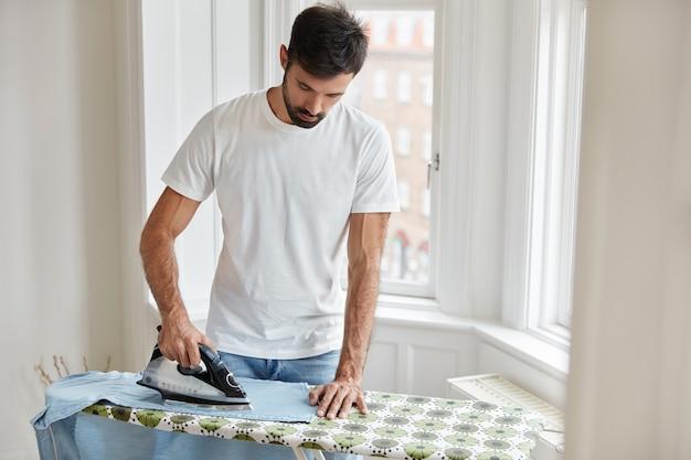 Knappe man strijkt kleren op de strijkplank Gratis Foto