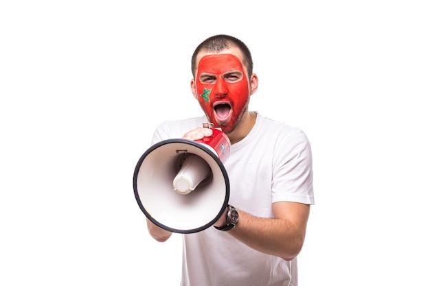 Knappe man supporter loyale fan van marokko nationale team geschilderd vlag gezicht krijgen gelukkige overwinning schreeuwen in megafoon met puntige hand. fans van emoties. Gratis Foto