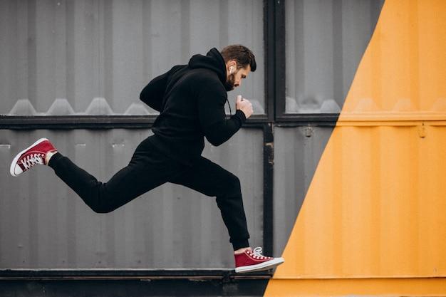 Knappe man uitoefenen in park in sportkleding Gratis Foto