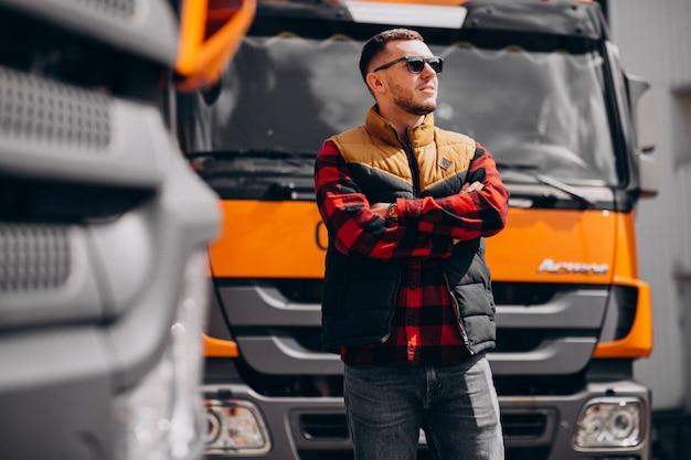 Knappe man vrachtwagenchauffeur permanent door de vrachtwagen Gratis Foto