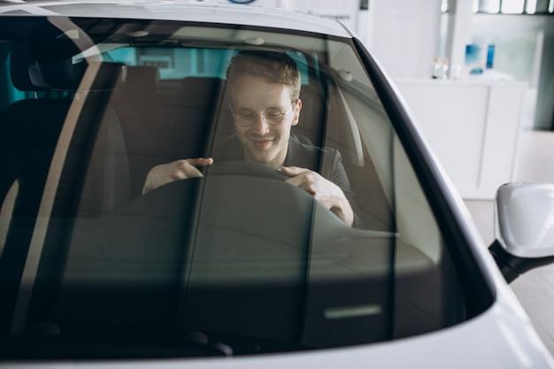 Knappe man zit in een auto Gratis Foto