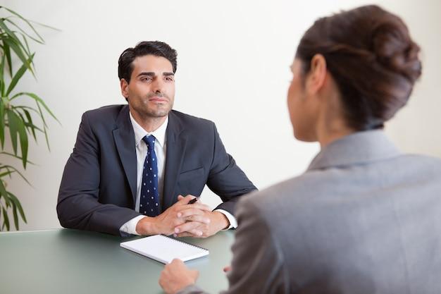 Knappe manager die een vrouwelijke kandidaat interviewt Premium Foto