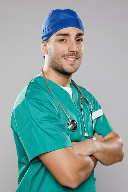 Knappe mannelijke arts poseren met gekruiste armen Gratis Foto