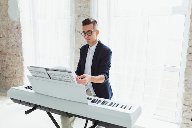 Knappe mannelijke pianospeler die de pagina's van muzikaal blad op piano draait Gratis Foto
