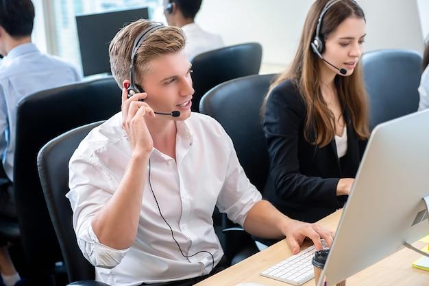 Knappe mens die als klantenverzorgingspersoneel werkt met team in call centre Premium Foto