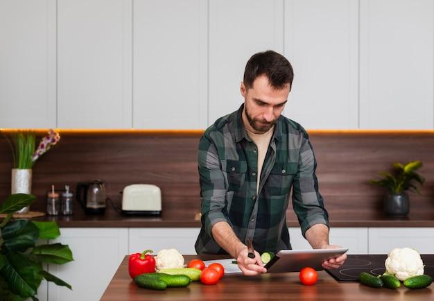 Knappe mens die op tablet in keuken kijkt Gratis Foto