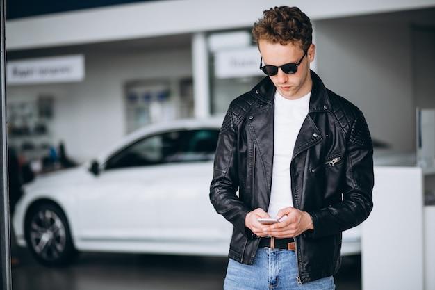Knappe mens die telefoon in een autotoonzaal met behulp van Gratis Foto