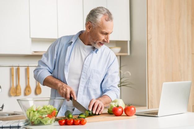Knappe mens die zich bij de keuken bevindt die laptop en het koken gebruikt Gratis Foto