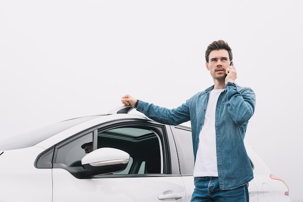 Knappe mens die zich dichtbij de auto bevindt die op cellphone spreekt Gratis Foto