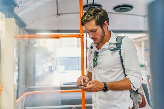 Knappe mens die zich in stadsbus bevindt en een bericht op de telefoon typt. Premium Foto