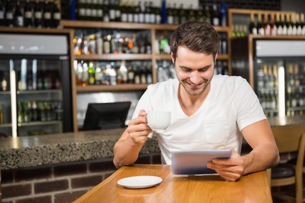 Knappe mens gebruikend tablet en hebbend koffie Premium Foto