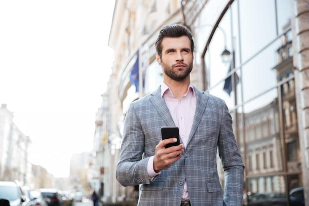 Knappe mens in een jasje die en mobiele telefoon lopen houden Gratis Foto