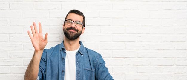 Knappe mens met baard over het witte bakstenen muur groeten met hand met gelukkige uitdrukking Premium Foto