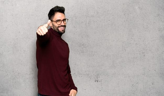Knappe mens met glazen het geven van duimen op gebaar omdat iets goeds is gebeurd over geweven muur Premium Foto