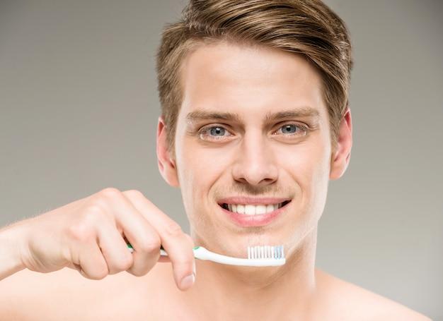 Knappe mensen schoonmakende tanden met tandenborstel in badkamers. Premium Foto