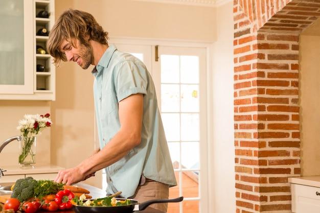 Knappe mensen snijdende groenten in de keuken Premium Foto
