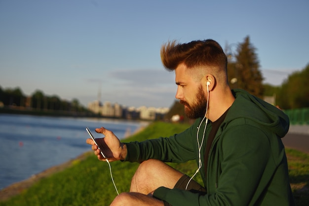 Knappe modieuze jongeman met stijlvol kapsel en dikke baard genieten van rustige zomerochtend buiten, zittend aan het meer en luisteren naar muzieknummers met behulp van de online app op zijn mobiele telefoon Gratis Foto