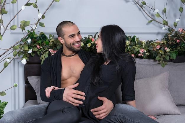 Knappe moslim man zittend op het bed met zijn mooie zwangere vrouw, haar buik knuffelen en glimlachen Premium Foto