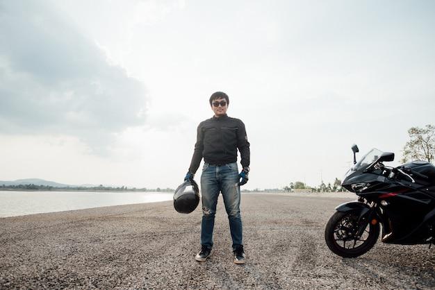 Knappe motorrijder met helm in handen van motorfiets Gratis Foto
