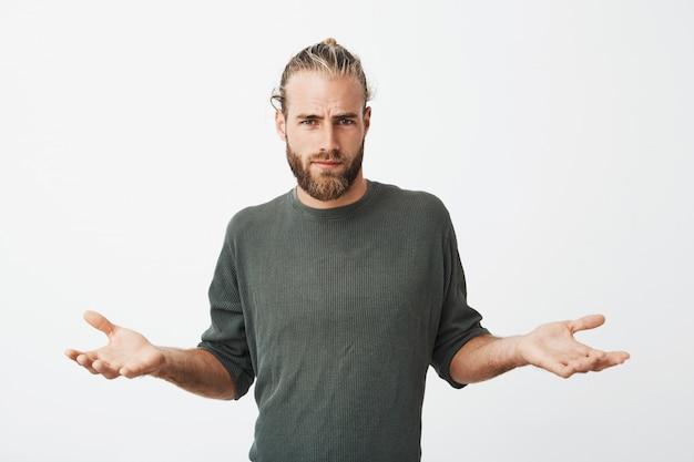 Knappe nordic man met baard en stijlvol kapsel spreidt handen met cynische en gemene uitdrukking Gratis Foto