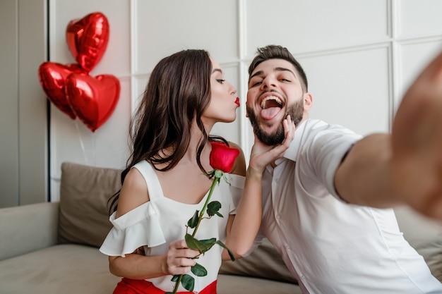 Knappe paar man en vrouw maken selfie met rode roos en hartvormige ballonnen thuis op de bank Premium Foto