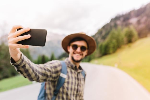 Knappe reiziger poseren op italiaanse natuur landschap en glimlachen, genieten van actieve vakantie Gratis Foto