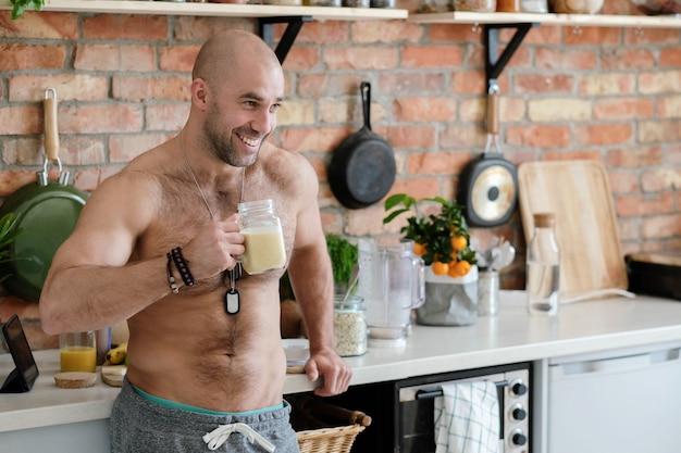 Knappe, shirtloze man in de keuken Gratis Foto