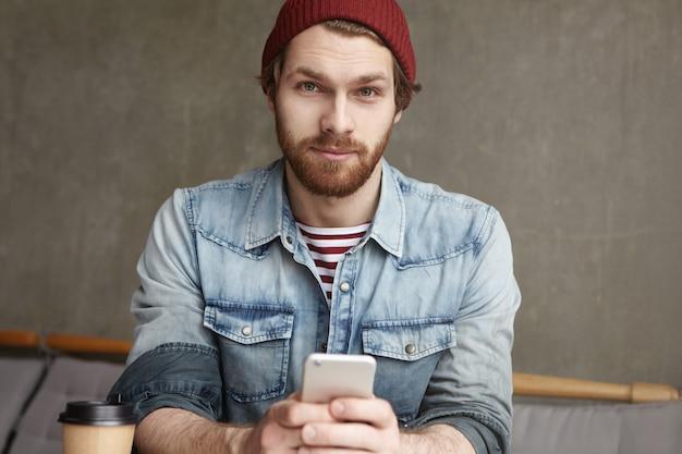Knappe stijlvolle jonge blanke man met mobiele telefoon, sms'en van zijn vriendin, haar vragen om een wandeling te maken op een warme lentedag zittend in een café, genietend van verse koffie in een papieren beker Gratis Foto