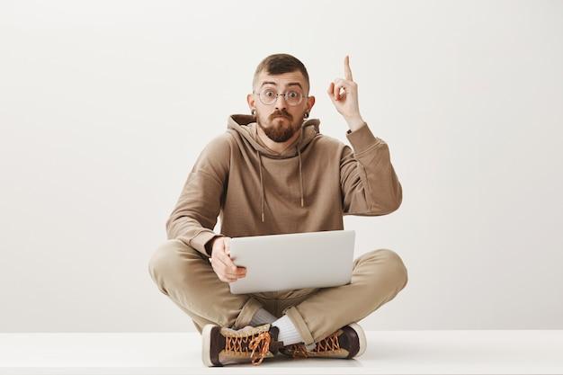 Knappe student zit op gekruiste benen met laptop en wijsvinger op, heb een goed idee Gratis Foto