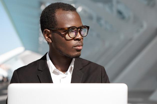 Knappe succesvolle jonge afro-amerikaanse bedrijfsmedewerker in brillen en zwart pak buiten zitten voor laptop pc, wegkijken, nadenkende uitdrukking, verzonken in zakelijke kwesties Gratis Foto