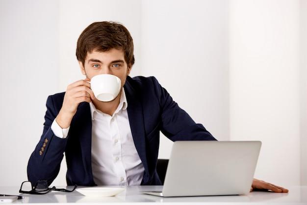 Knappe succesvolle zakenman in pak, zit zijn kantoor met laptop, koffie drinken, klaar productief werk Gratis Foto