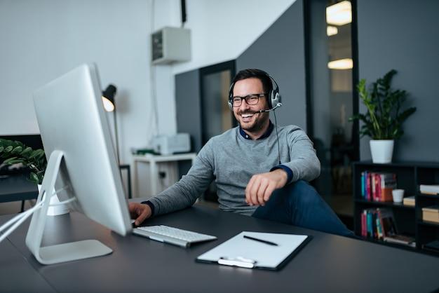 Knappe toevallige zakenman die online via hoofdtelefoon spreekt. Premium Foto
