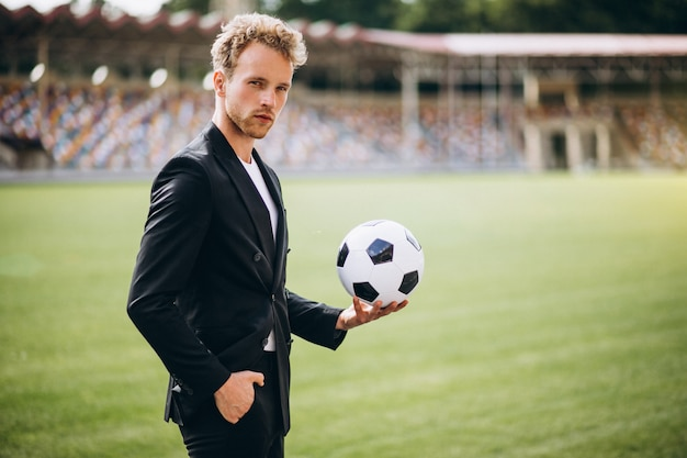 Knappe voetballer bij stadion in pak Gratis Foto