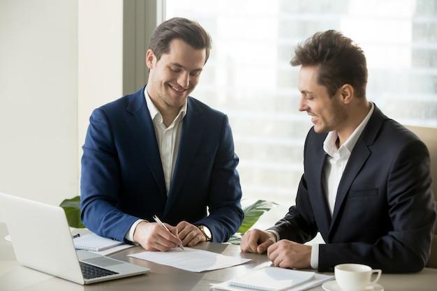 Knappe zakenman die contract met partner ondertekent Gratis Foto