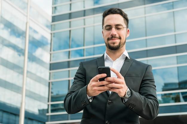 Knappe zakenman die van tekstoverseinen op mobiele telefoon geniet Gratis Foto