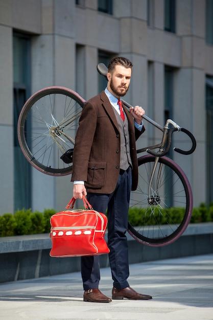 Knappe zakenman die zijn fiets draagt Gratis Foto