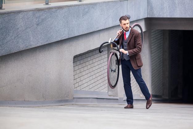 Knappe zakenman die zijn fiets op stadsstraten draagt. het concept van de moderne levensstijl van jonge mannen Gratis Foto