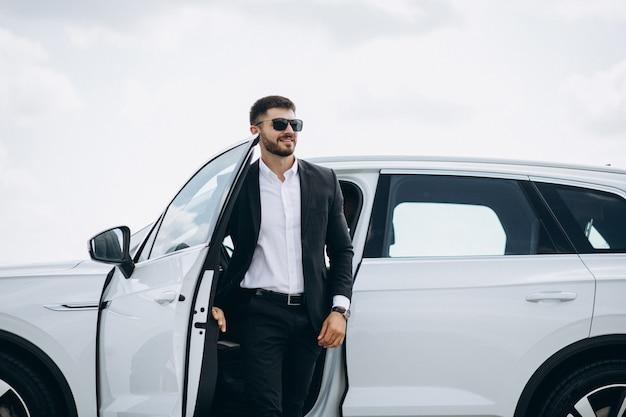 Knappe zakenman door de witte auto Gratis Foto