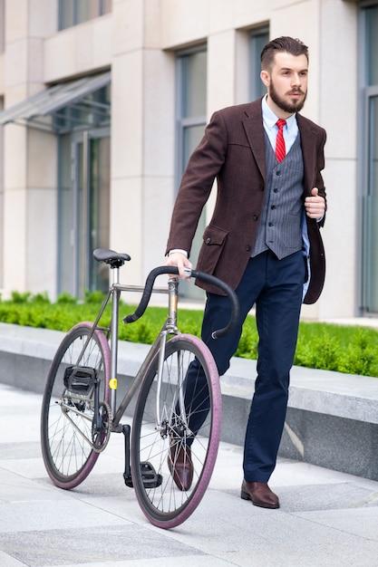 Knappe zakenman in een jas en een rode stropdas en zijn fiets op stadsstraten. Gratis Foto