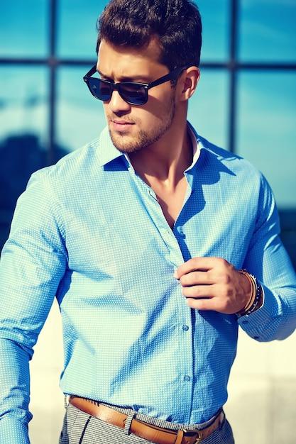 Knappe zakenman in formele kleding poseren in de straat in zonnebril Gratis Foto