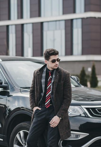 Knappe zakenman in glazen die zich dichtbij auto bevinden. leenauto Premium Foto