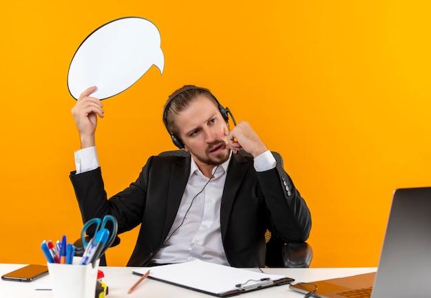 Knappe zakenman in pak en koptelefoon met een microfoon met lege tekstballon teken opzij kijken verbaasd zittend aan tafel in het kantoor over oranje achtergrond Gratis Foto
