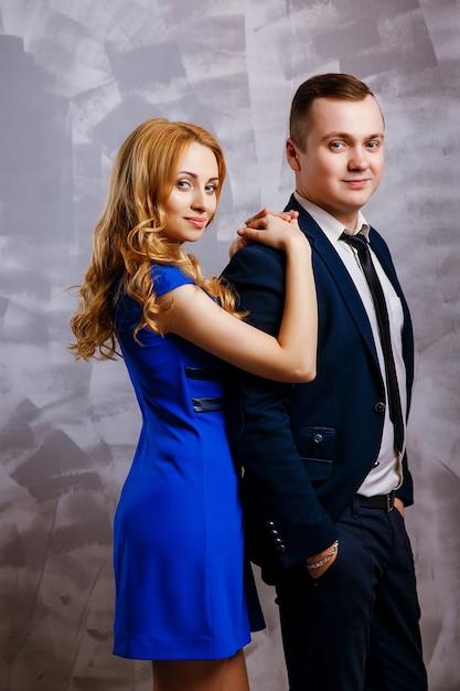 Knappe zakenman in pak poseren met mooie blonde vrouw in blauwe jurk Premium Foto