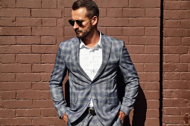Knappe zakenman mannequin gekleed in elegante geruite pak poseren in de buurt van bakstenen muur op straat Gratis Foto