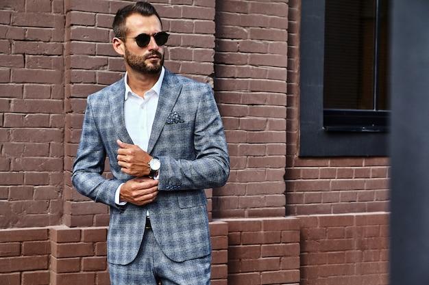Knappe zakenman mannequin gekleed in elegante geruite pak poseren op straat Gratis Foto