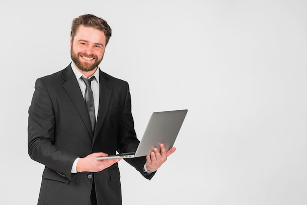 Knappe zakenman met behulp van laptop en glimlachen Gratis Foto