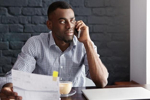 Knappe zelfverzekerde afro-amerikaanse zakenman die administratie doet Gratis Foto