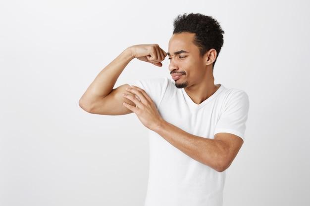 Knappe zelfverzekerde en sterke afro-amerikaanse man buigen biceps, trainen in de sportschool, brutaal op zoek Gratis Foto