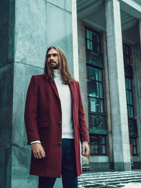 Knappe zelfverzekerde goed geklede man met baard poseren buitenshuis wegkijken. modieus rijk mannelijk model in rode winterjas en witte trui Gratis Foto
